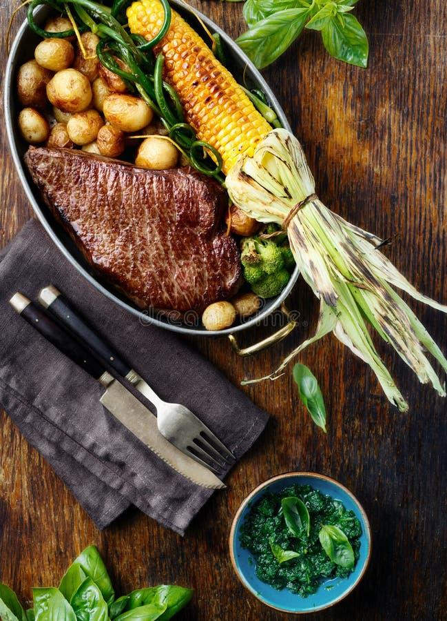 在煎锅的水多的牛排有菜顶视图 免版税图库摄影