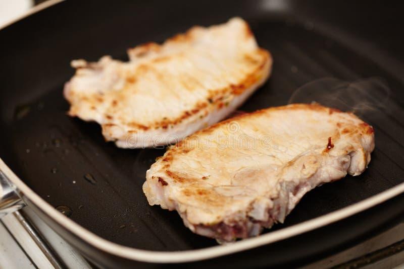 在煎锅的油煎的猪排 免版税库存照片