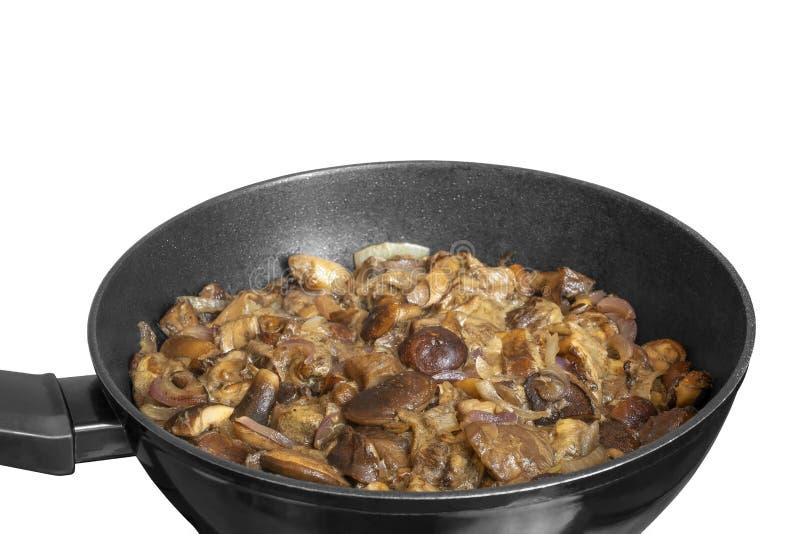 在煎锅的油煎的Imleria badia蘑菇 煮熟的牛肝菌蕈类badius用在白色背景隔绝的平板炉的葱 库存照片