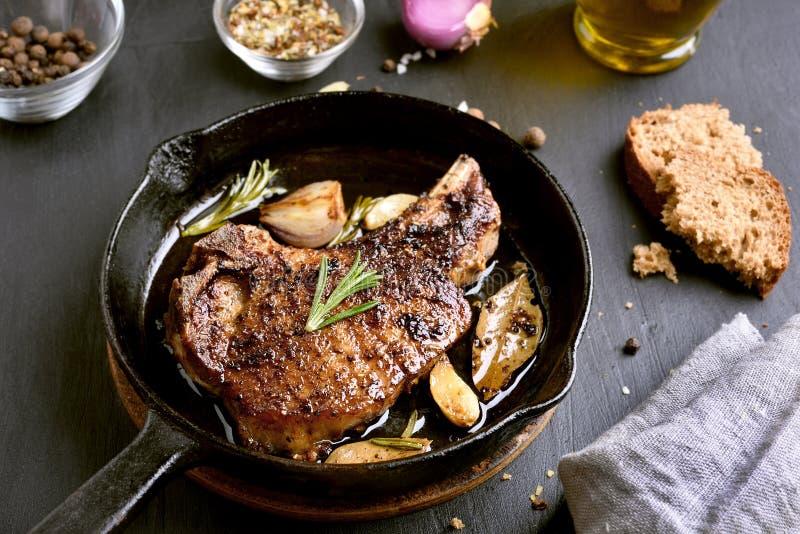 在煎锅的烤猪肉牛排 免版税图库摄影