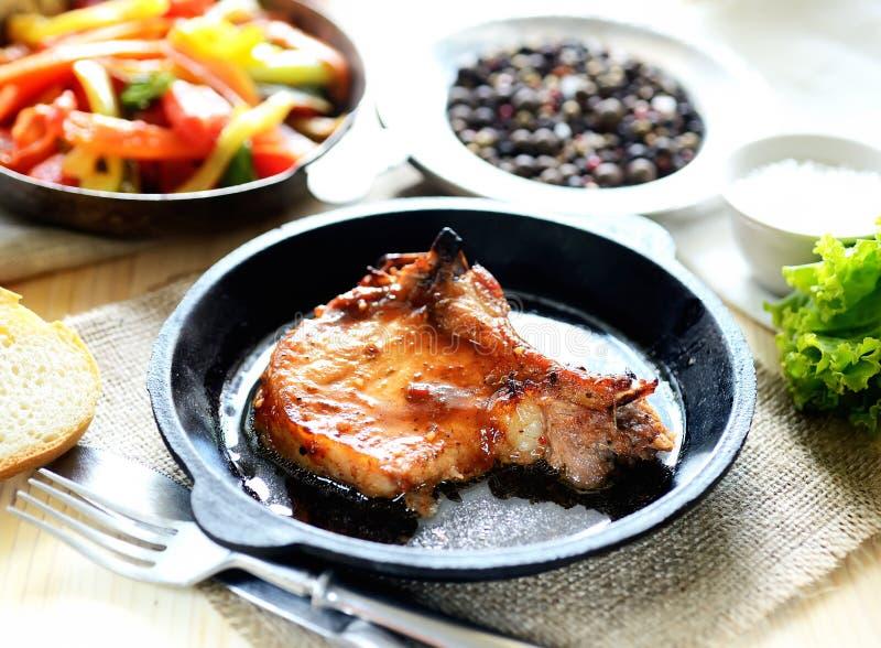 在煎锅的猪肉牛排,油煎的菜 免版税库存图片