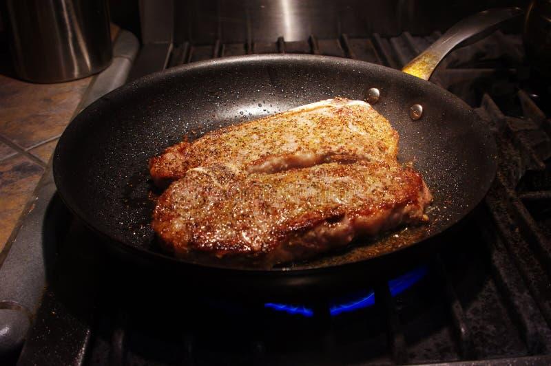 在煎锅的纽约牛排 图库摄影