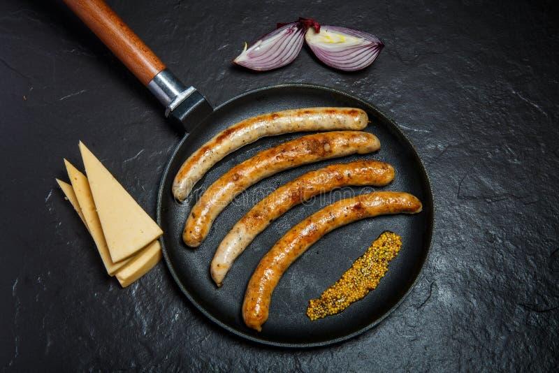 在煎锅的顶视图用油煎的稀薄的香肠和颗粒状芥末 图库摄影