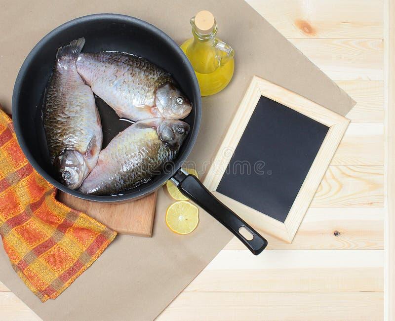 在煎锅的鲤鱼有菜油和柠檬的在牛皮纸,在黑板旁边 免版税库存图片