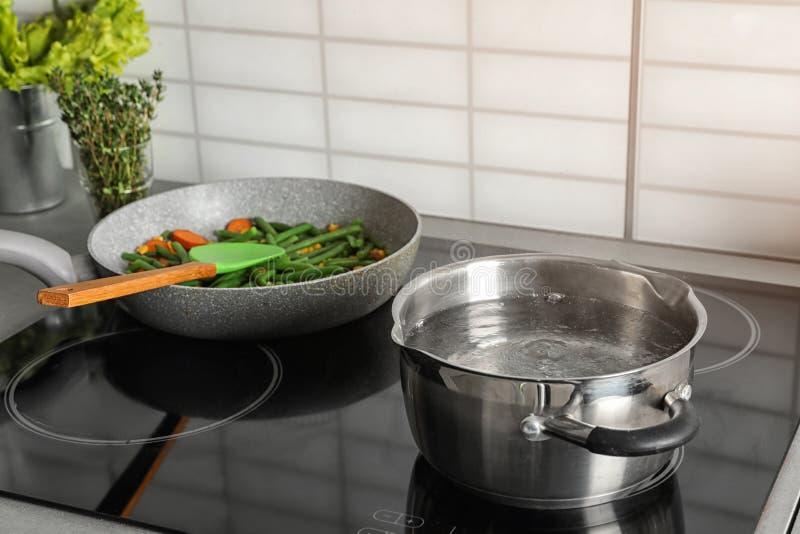 在煎锅附近的罐有在电火炉的菜的 免版税库存照片