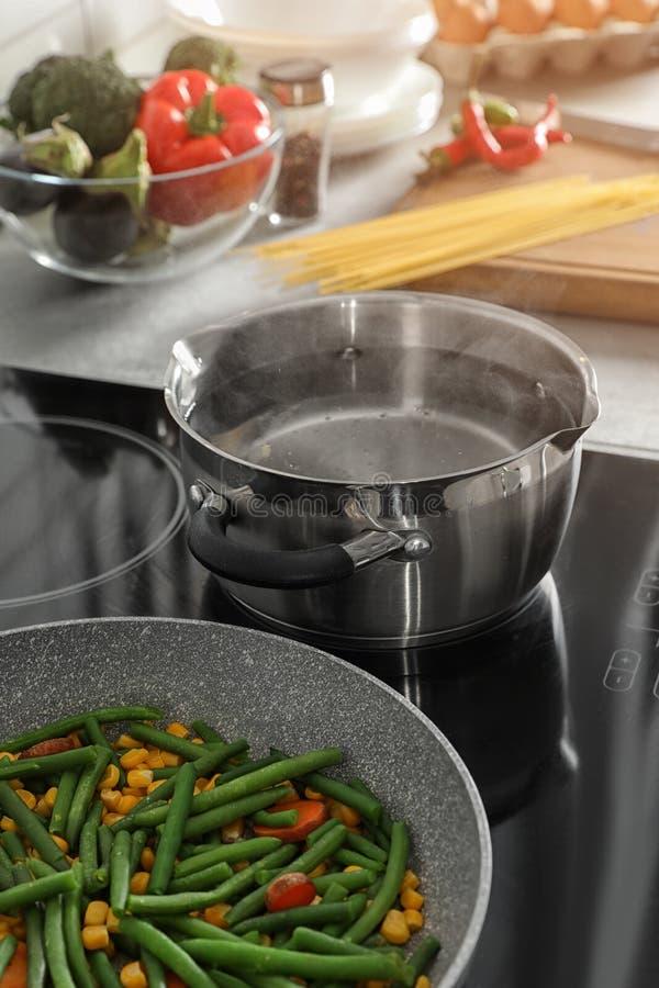 在煎锅附近的罐有在电火炉的菜的 库存照片
