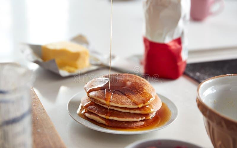 在煎饼日,桌上铺着一叠新做的煎饼或薄饼的枫糖浆 免版税库存图片