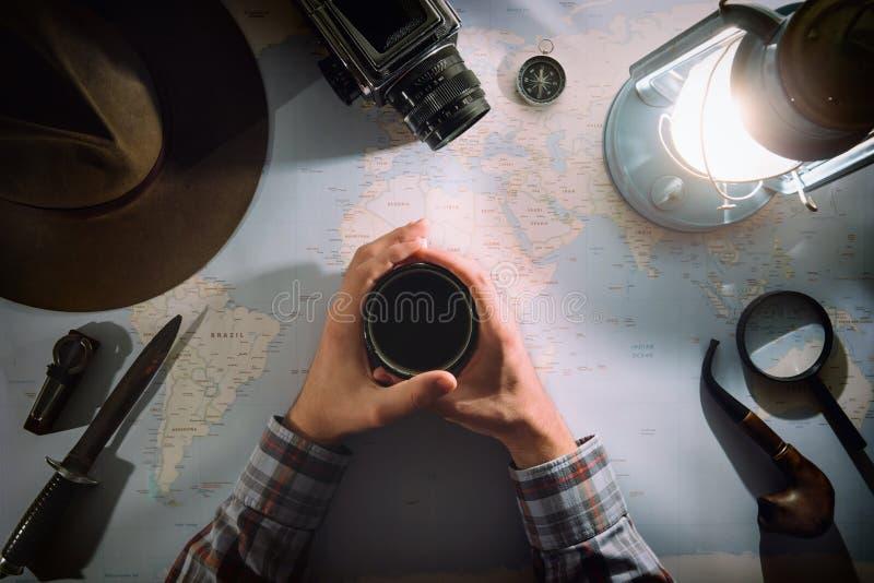 在煤气灯平的位置附近的冒险计划 在地图的大气老齿轮 旅客,在框架藏品茶的探险家手或 免版税库存照片