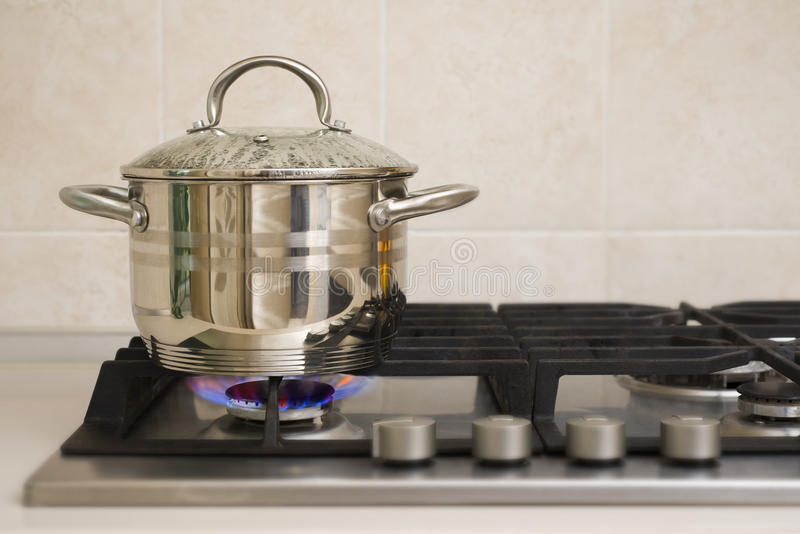 在煤气炉火的煮沸的罐 库存图片