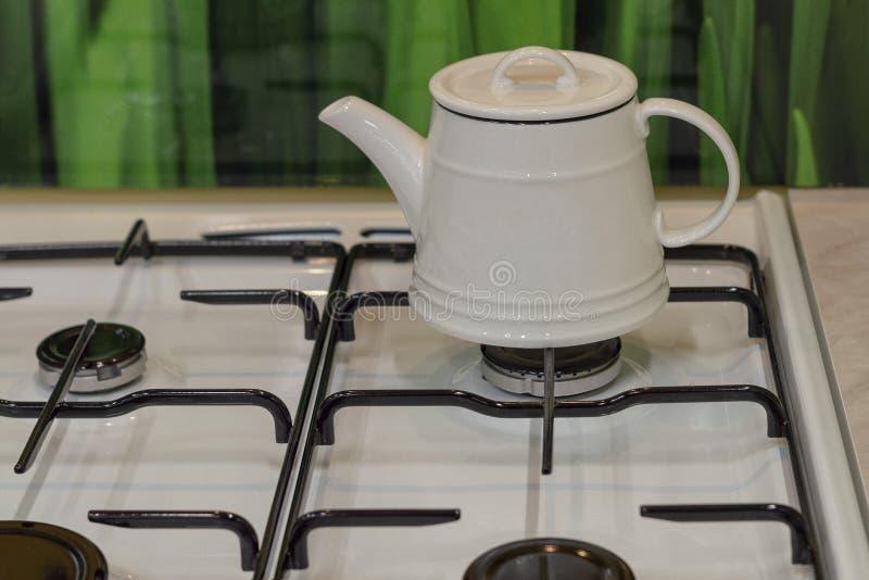 在煤气炉的白色水壶在厨房里 图库摄影