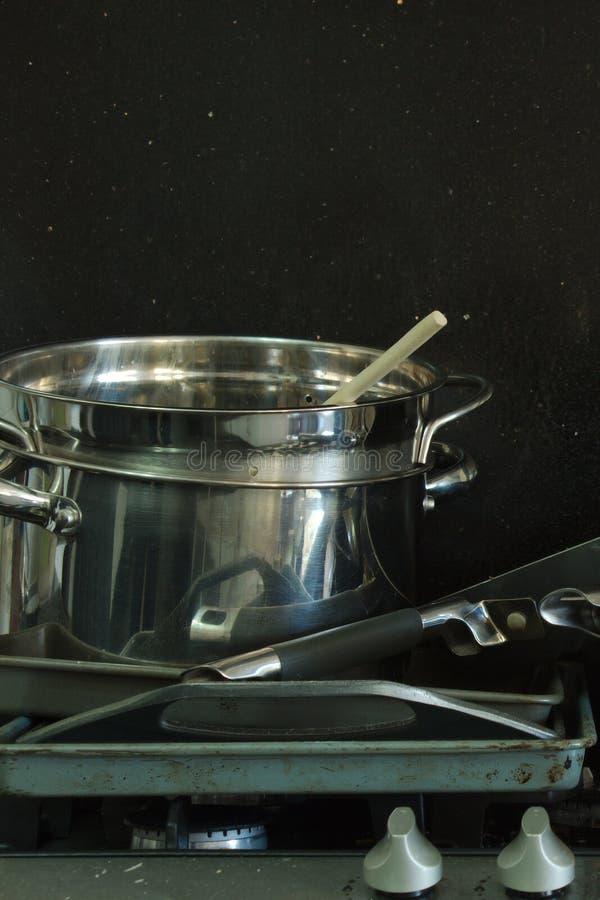 在煤气炉的肮脏的平底锅有黑背景3 库存图片