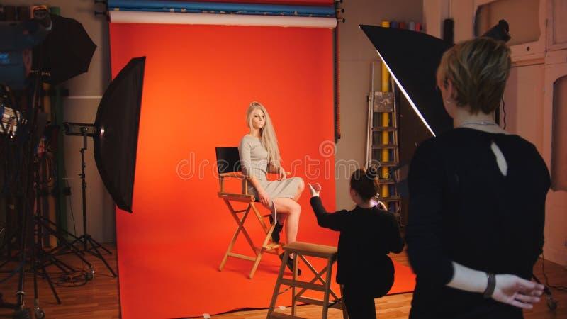 在照片演播室的白肤金发的式样女孩-摄影师和做艺术家调直头发,后台的时尚 库存照片