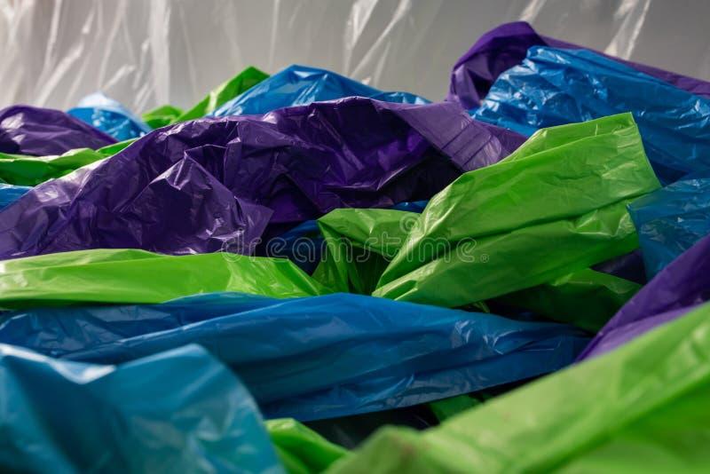 在照相机一起交错的五颜六色的便宜的塑料袋 免版税库存图片