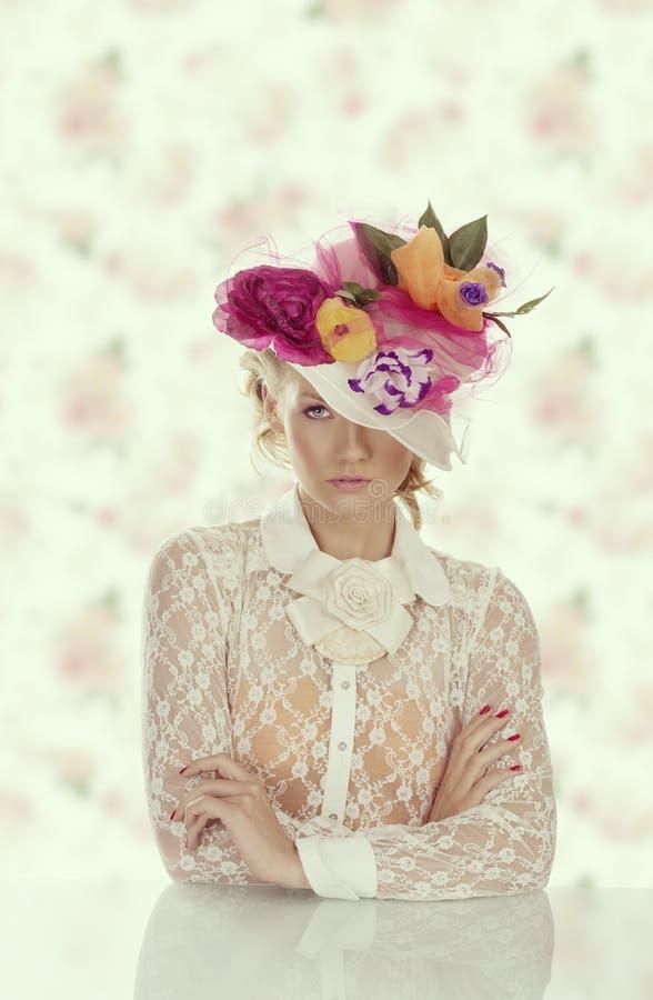 在照相机前面的典雅的女孩在与花卉帽子的桌后 免版税图库摄影