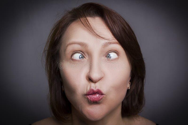在照相机前面的妇女鬼脸 免版税库存照片