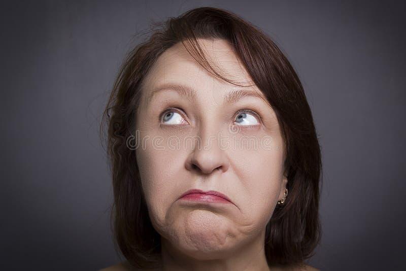 在照相机前面的妇女鬼脸 免版税库存图片