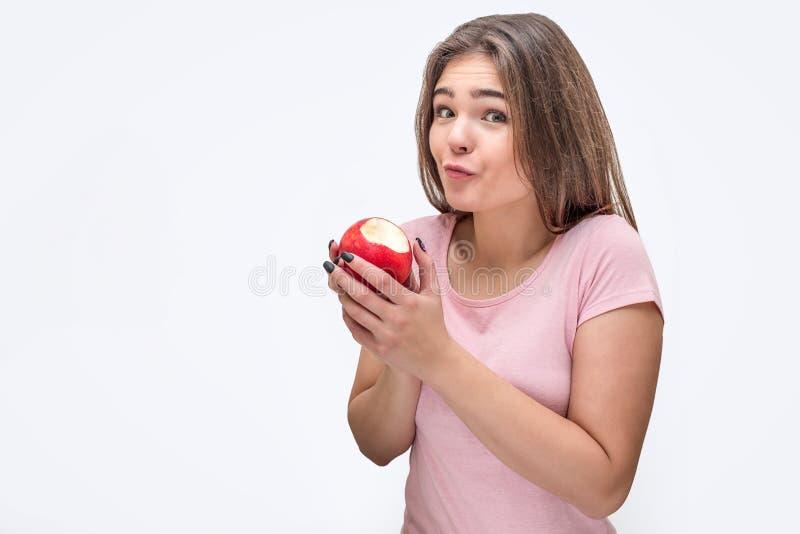 在照相机的好和有吸引力的年轻女人神色和拿着被咬住的苹果 她惊奇 背景查出的白色 库存图片