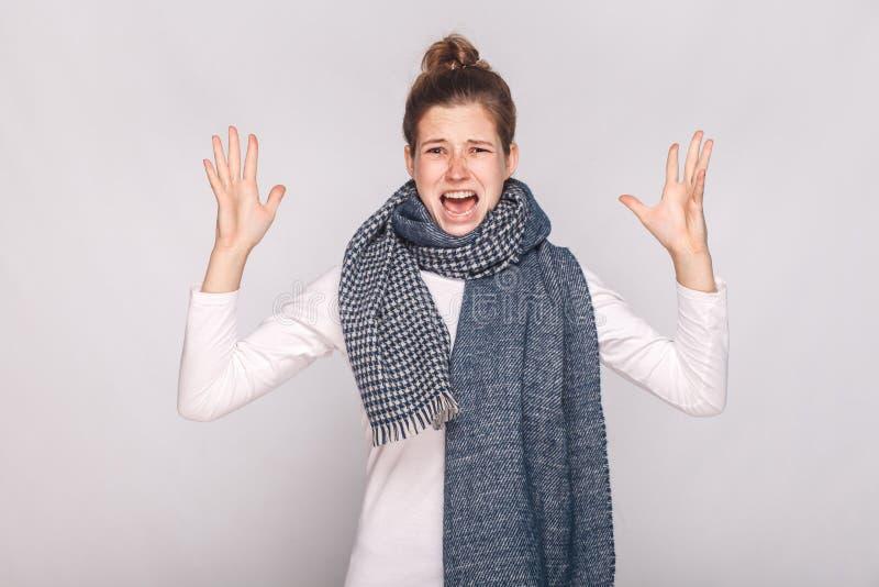 在照相机的恼怒的病态的妇女吼声和有不适的神色 免版税库存图片