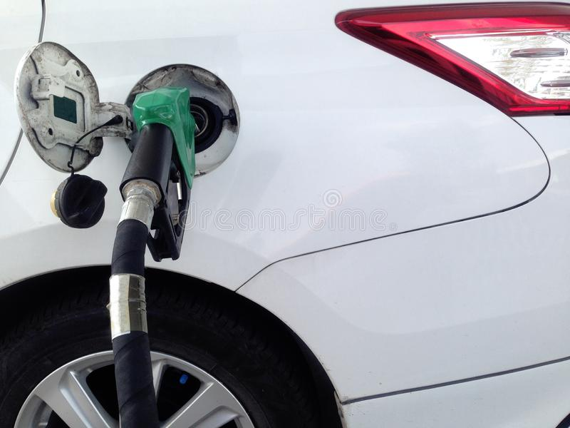 在燃料驻地的白色汽车燃料补白 在加油站的燃料分配器 库存图片