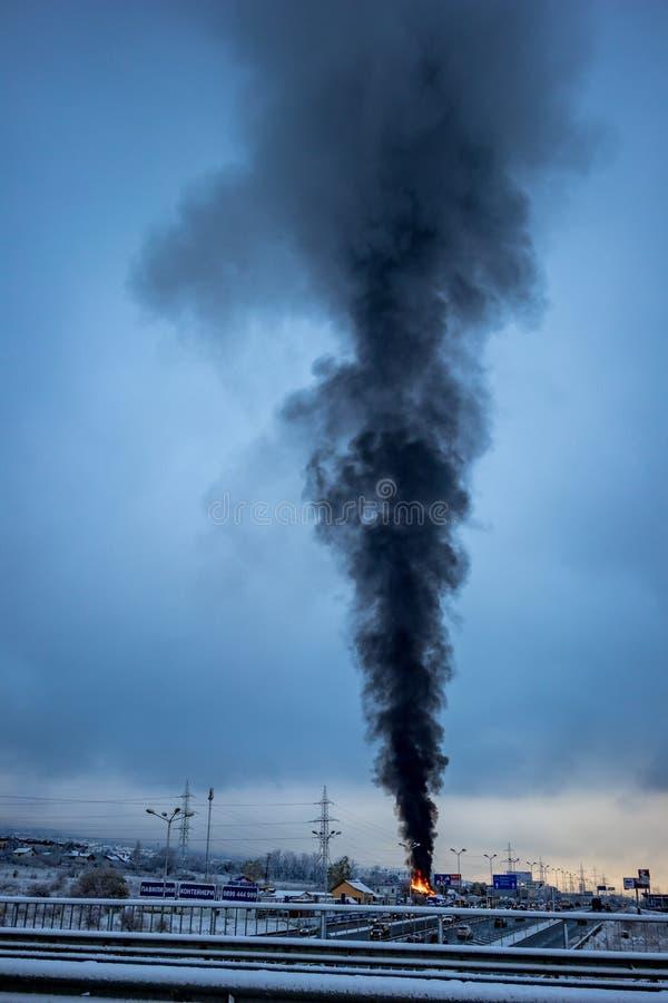 在燃烧的仓库上的巨大的黑烟在索非亚 库存图片