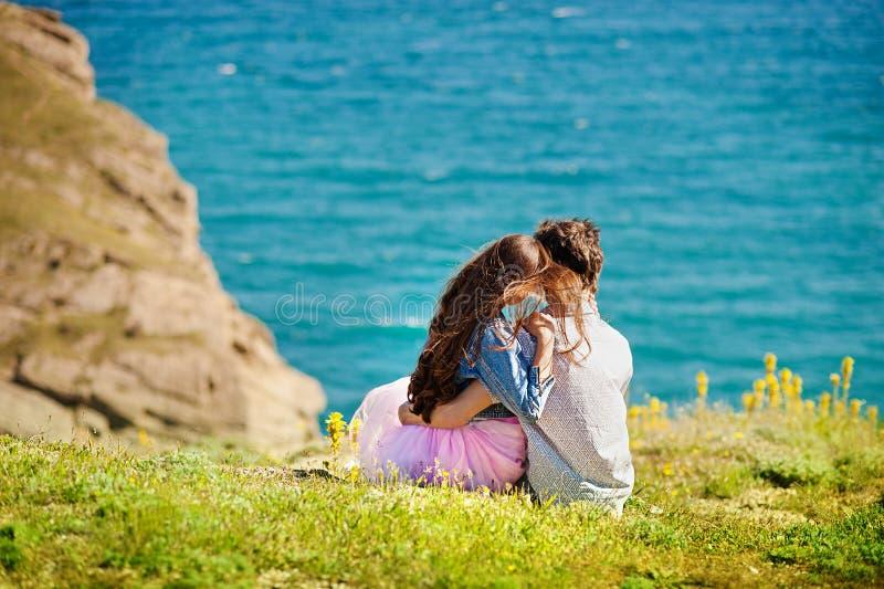在爱、可爱的享受在海滩的男人和妇女的年轻夫妇浪漫晚上观看日落 库存照片