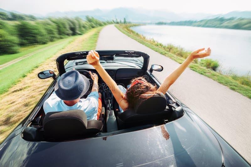 在爱乘驾的夫妇在敞蓬车汽车 库存图片