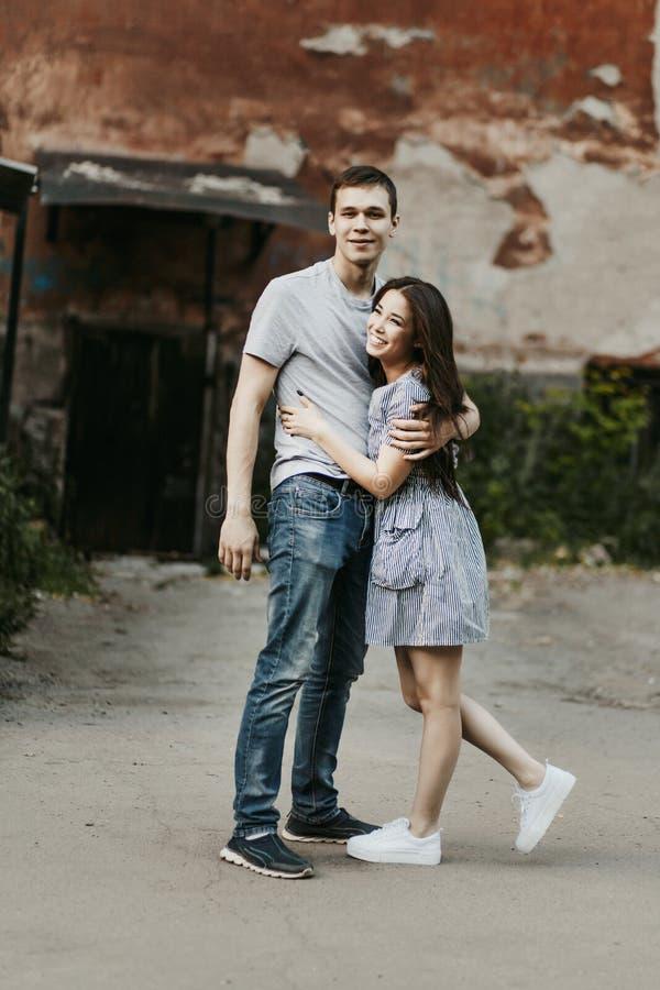 在爱在便装样式打扮的少年朋友的愉快的年轻夫妇一起走在老城市街道上 库存照片