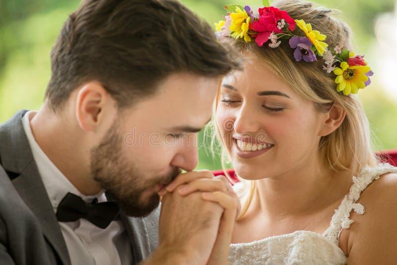 在爱婚礼新娘和新郎亲吻的手的年轻夫妇在公园 新婚佳偶 特写镜头画象美丽有  库存图片