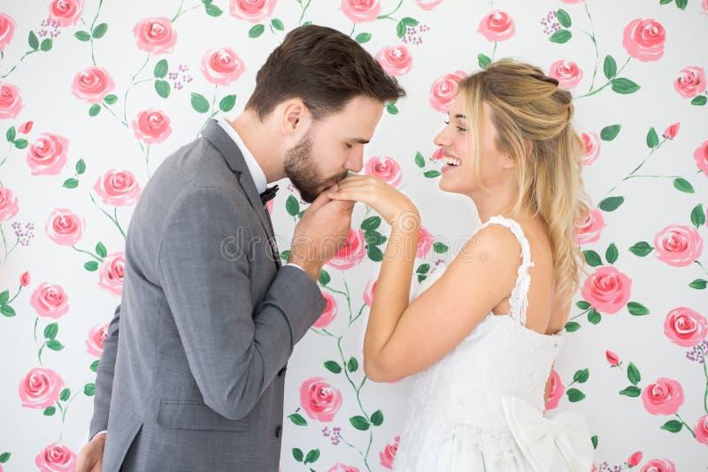 在爱婚礼新娘和新郎亲吻的手的年轻夫妇在玫瑰背景 新婚佳偶 特写镜头画象美丽有  免版税库存照片