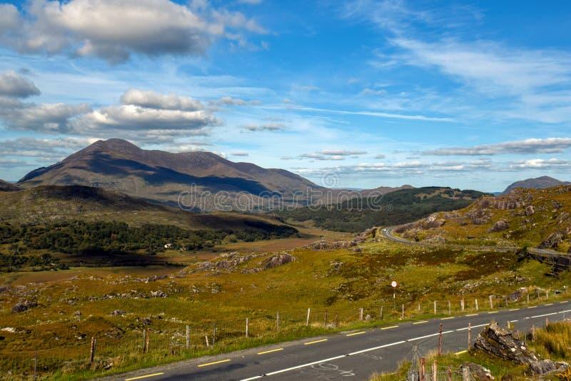 在爱尔兰的青山的中狭窄的柏油路绕 女人造成缝隙 凯利环形 库存图片