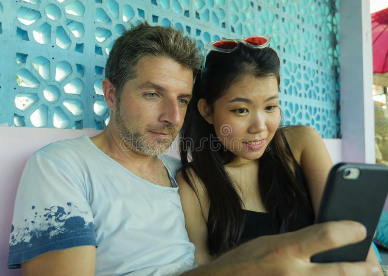 在爱微笑的混杂的种族夫妇快乐与英俊的白种人男人和使用手机的美丽的亚裔中国妇女 图库摄影