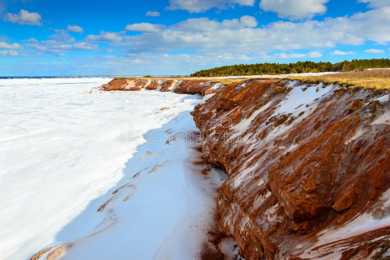在爱德华王子岛的北部岸的被冰的红色峭壁 免版税库存图片