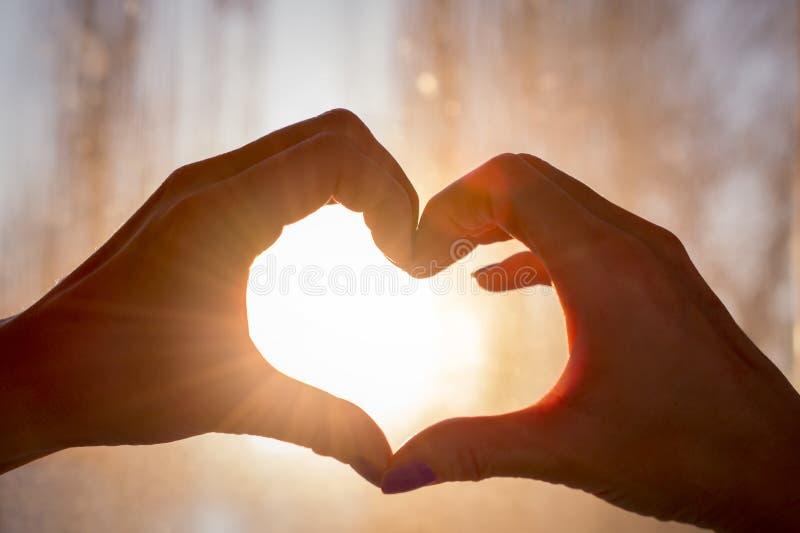 在爱心脏形状的手现出轮廓反对太阳 免版税图库摄影
