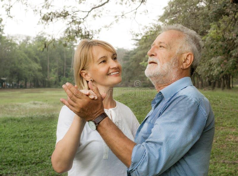 在爱愉快在公园,跳舞和有乐趣,幸福生活的愉快的微笑的资深夫妇 库存图片