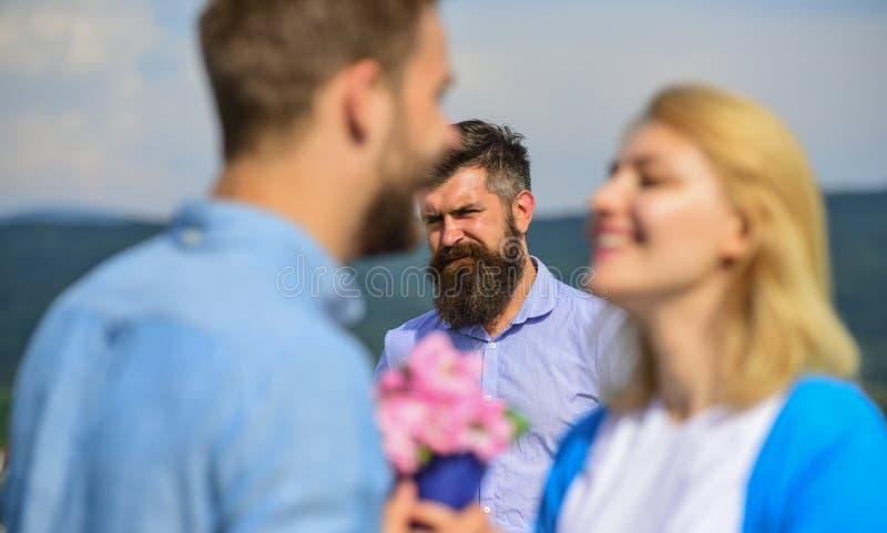 在爱愉快的约会的夫妇,嫉妒的有胡子的欺诈他的人观看的妻子与恋人 遇见室外调情的人的恋人 库存图片