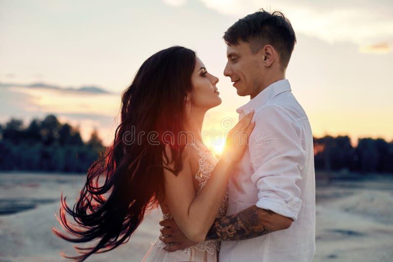 在爱拥抱的夫妇在眼睛亲吻愉快的生活、男人和妇女,日落,太阳光芒,在看的爱的一对夫妇 图库摄影