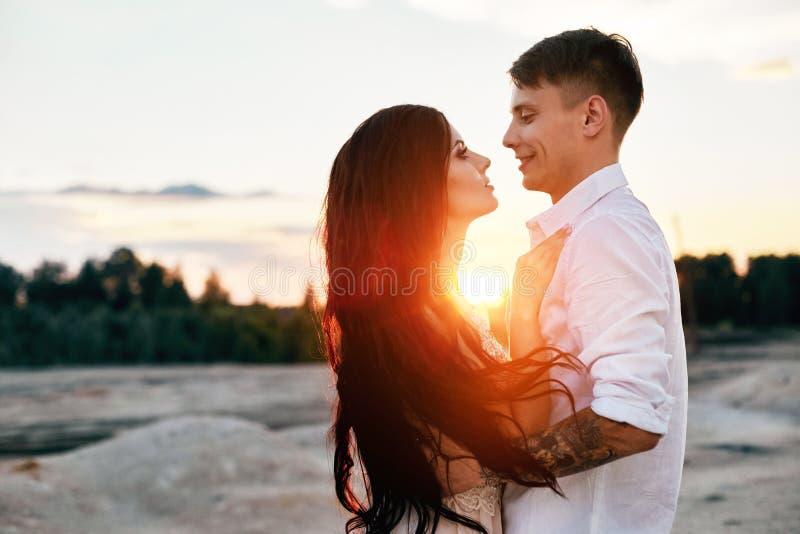 在爱拥抱的夫妇在眼睛亲吻愉快的生活、男人和妇女,日落,太阳光芒,在看的爱的一对夫妇 免版税库存照片