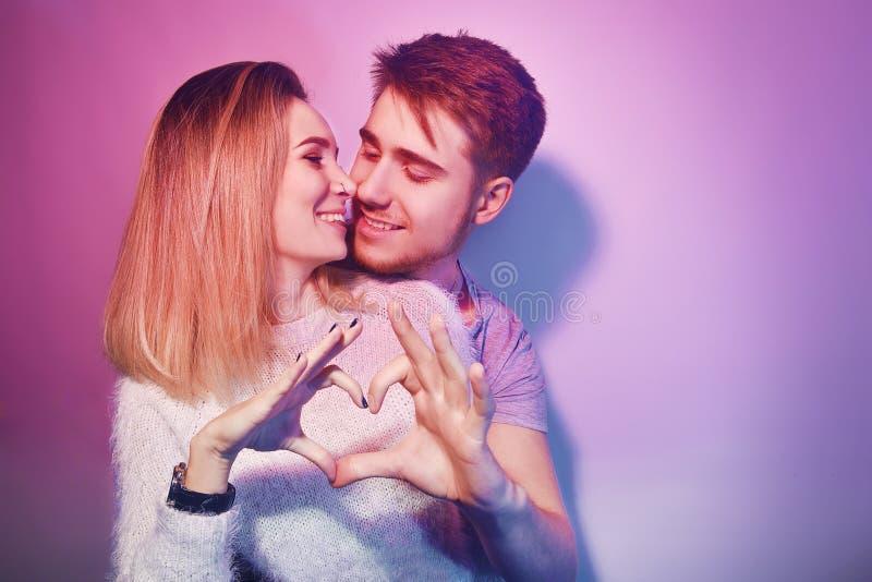 在爱拥抱的年轻夫妇亲吻 爱 做心脏形状用手的夫妇特写镜头  情人节和爱 库存图片