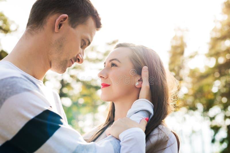 在爱拥抱的愉快的年轻夫妇 户外公园约会 夫妇爱 免版税库存照片