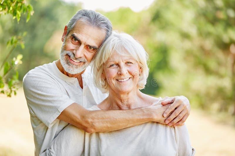 在爱拥抱的愉快的资深夫妇 免版税库存图片