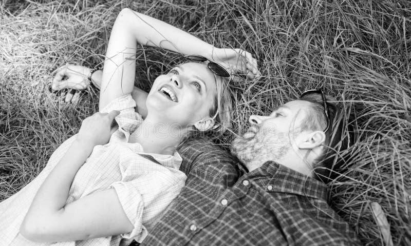 在爱放松的夫妇被放置在草甸 自然用生气勃勃和和平填装他们 不剃须在草放置的人和女孩 图库摄影