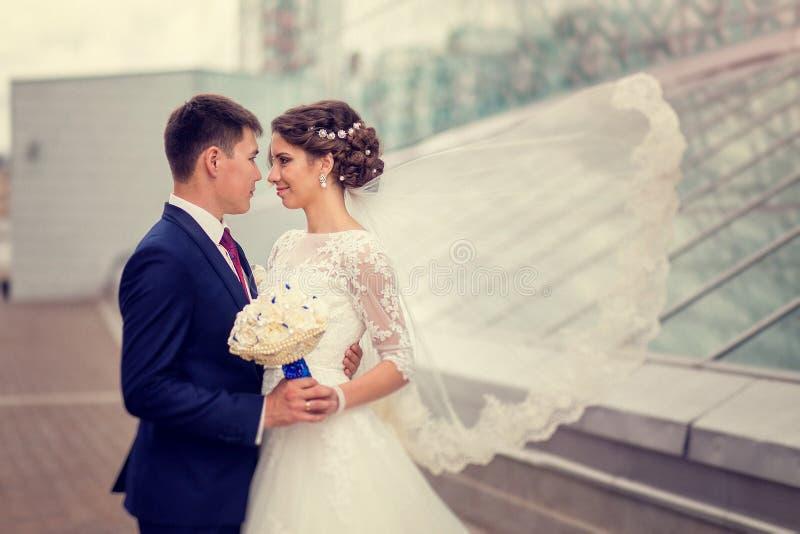 在爱新娘和新郎容忍的夫妇在都市建筑学背景  振翼在风的新娘的面纱 图库摄影