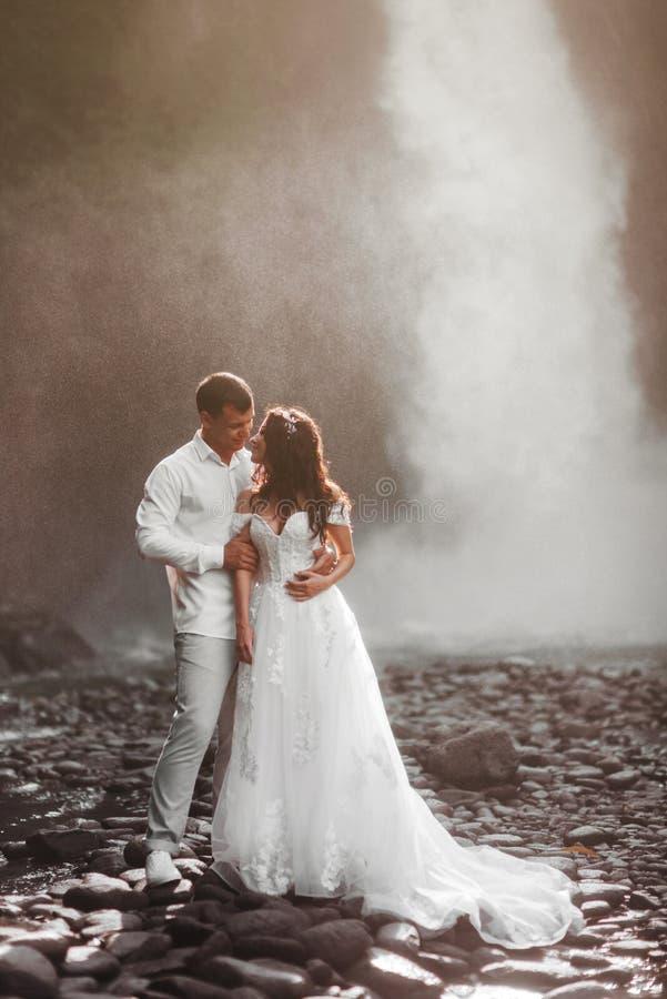 在爱新娘和新郎,在山瀑布附近的婚礼那天的年轻夫妇 免版税图库摄影