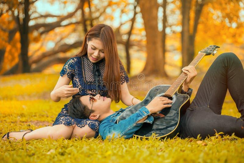 在爱的亚洲年轻夫妇在有太阳光的庭院秋天公园享用弹吉他的人说谎在女朋友腿 免版税库存图片