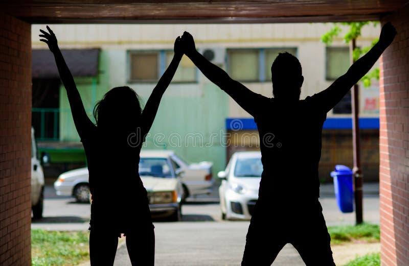 在爱的剪影夫妇反对都市背景 夫妇集会在门廊或门厅里 青年时期在日期花费时间 免版税库存照片