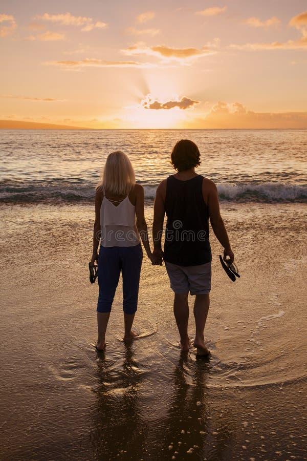 在爱的夫妇和举行手在海滩在日落 免版税图库摄影