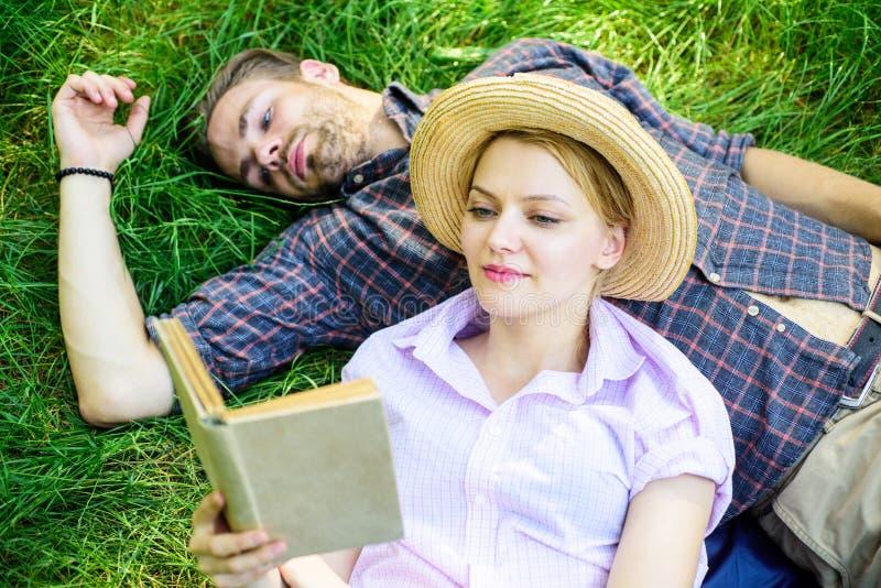 在爱的夫妇在公园花费休闲阅读书 夫妇知己在浪漫日期 家庭享受与诗歌的休闲 免版税库存图片