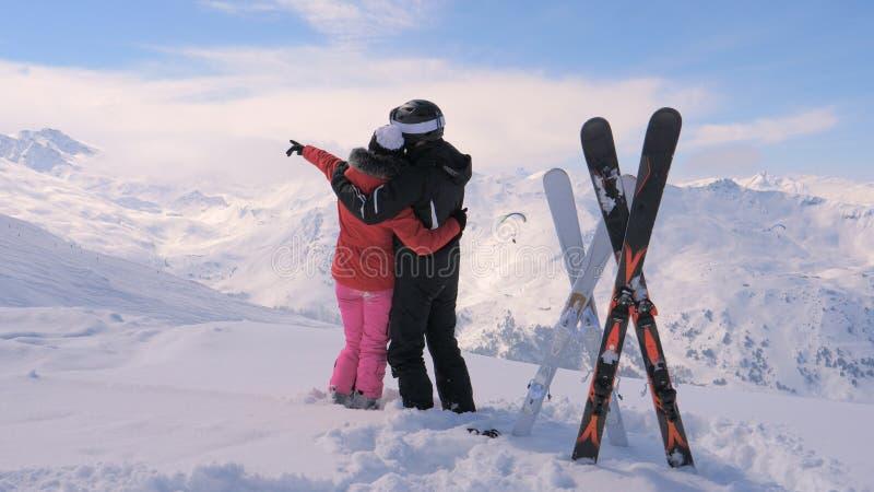 在爱的夫妇在斯诺伊山的上面站立并且移动他们的手 库存照片