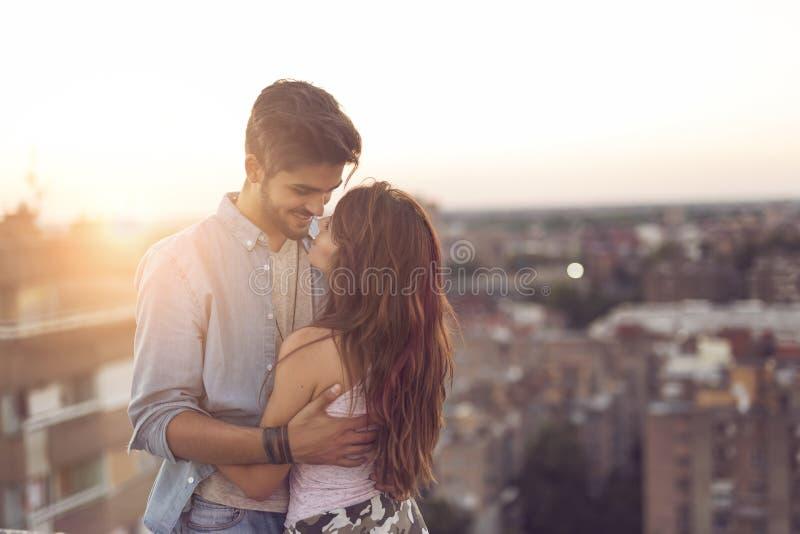 在爱的夫妇在日落的一个大厦屋顶 免版税库存图片