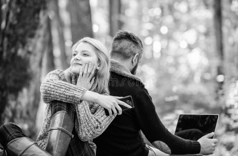 在爱的夫妇在有电话和膝上型计算机的秋天森林里放松 愉快女孩作梦室外 人坐与后面 r 免版税库存图片